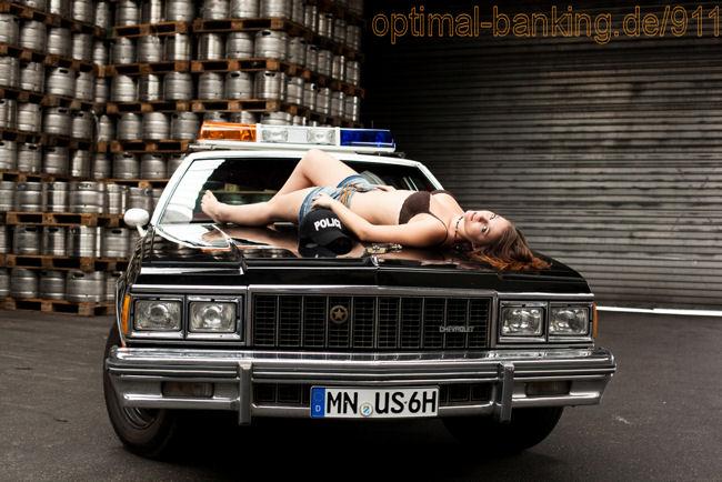 Model mit dem Rücken komplett auf der Moterhaube vom Police Car